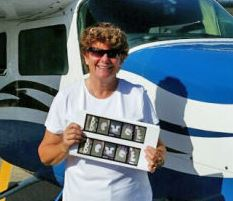 middle-aged woman standing in front of small plane holding up photographs