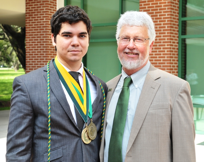 Young man in suit wearing medals on ribbons standing next to older man in suit