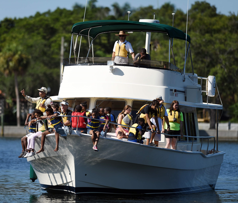 Crowd of children and adults on large white boat on the waterite