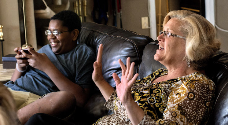 middle-aged white woman on couch gesturing with hands next to black teenager smiling and playing handheld video game