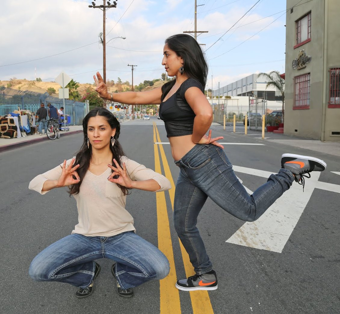 2 female dancers in street clothes performing in the street