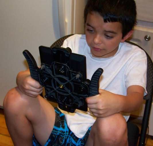 Boy using Pad-Go-Round to read with Kindle
