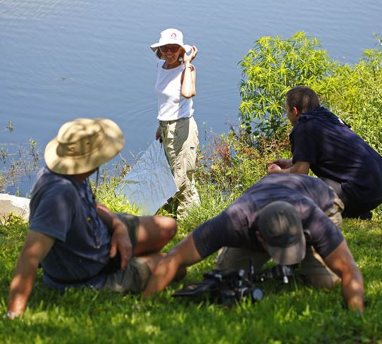Professor Deby Cassill at the edge of a lake with 3 members of BBC film crew