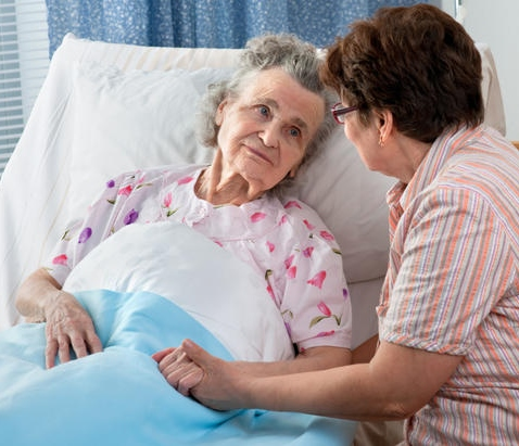 Elderly woman laying in bed with younger woman sitting next to her and holding her hand