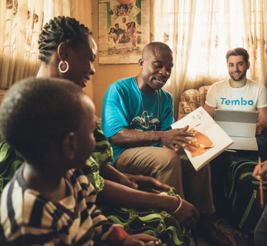 Young Nigerian child with smiling mother on couch with adult sharing book