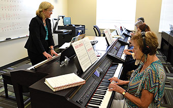 adult women wearing headphones and playing pianos facing instructor