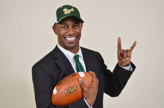 USF coach holding football, wearing ball cap, throwing horns
