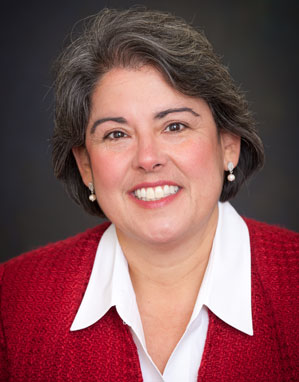Picture of Dr. Vasti Torres; she has black hair that is beginning to gray, has a smile on her face, and is wearing a red sweater